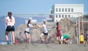 Two female soccer players high fiving on Ocean Beach in San Francisco.